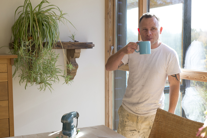 Man in white t-shirt standing, drinking from a blue mug