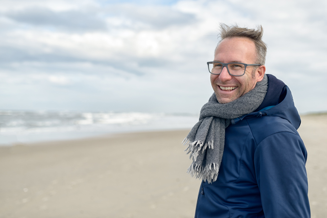 Man in blue jacket, wearing a scarf and standing on a beach