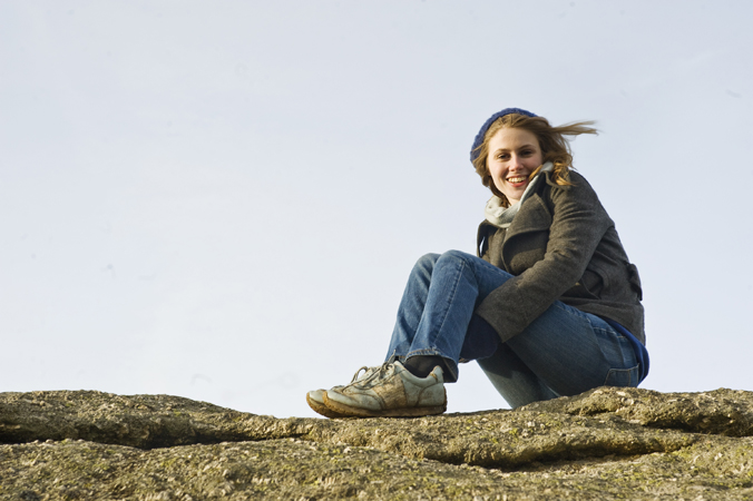 Young woman sitting on a rocky surface