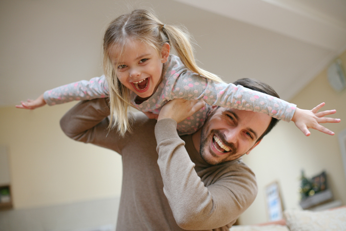 Father playing with his little girl who is on his shoulders