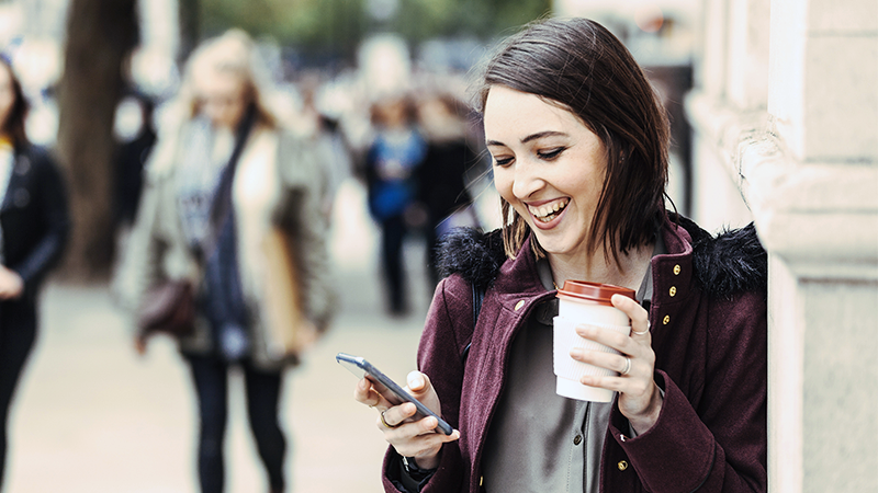 Woman outside, smiling, looking at phone and with a coffee cup in her hand