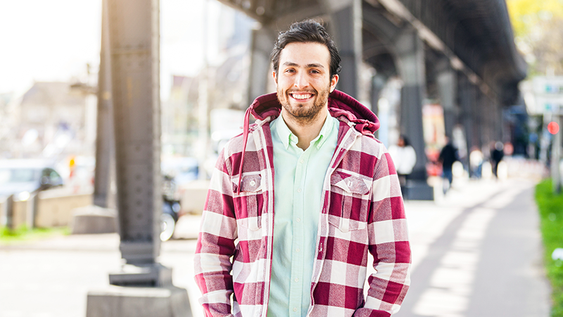 Smiling man in plaid jacket standing under a long bridge