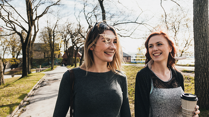 Two women out walking in a park, smiling