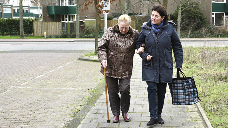 Carer supporting woman with her shopping