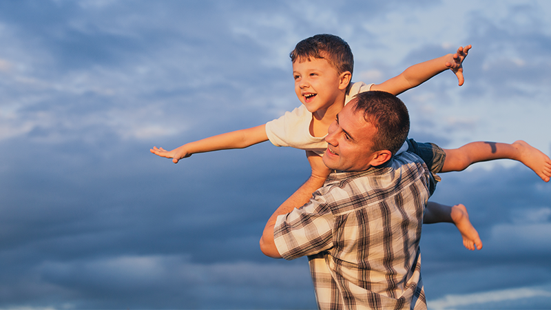 Man holding boy in the air, both smiling and boy looks like he is flying