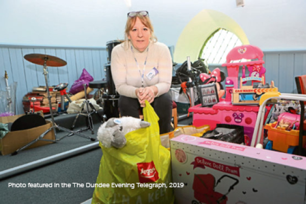 Lucie Conway sitting with gifts for Toy Recycle