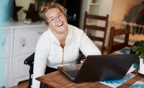 Getty 904516174 (Maskot) Portrait of smiling disabled woman using laptop at table in house