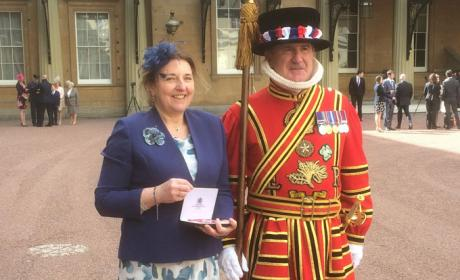 Paula showing MBE medal, standing beside a Beefeater