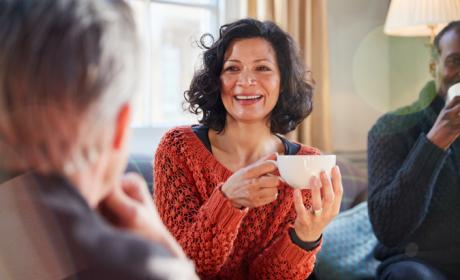 Woman in jumper smiling, holding a white cup and talking to people in a group