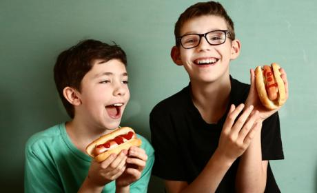 2 boys looking very happy to have hot dogs