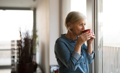 Thoughtful lady looking out of window and sipping a hot drink