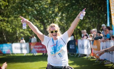 Finisher celebrating at end of Kiltwalk Challenge