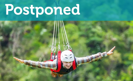 Man on zip wire with Postponed banner